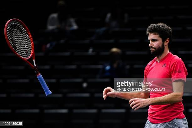 France's Gilles Simon reacts as he throws his racket on the ground while playing against Tommy Paul of the US during their men's singles first round...