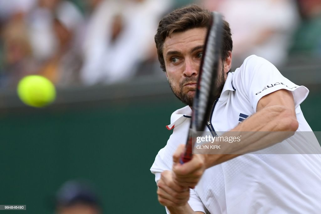 France's Gilles Simon returns against Argentina's Juan Martin del Potro during their men's singles fourth round match on the seventh day of the 2018 Wimbledon Championships at The All England Lawn Tennis Club in Wimbledon, southwest London, on July 9, 2018. (Photo by Glyn KIRK / AFP) / RESTRICTED