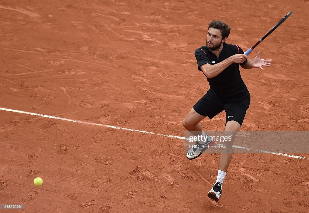 TOPSHOT - France's Gilles Simon returns the ball to Brazil's Rogerio Dutra Silva during their men's first round match at the Roland Garros 2016 French Tennis Open in Paris on May 23, 2016. / AFP / Eric FEFERBERG