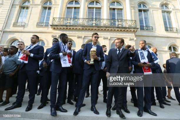 France's goalkeeper Alphonse Areola holds the winner's trophy as he stands next to French President Emmanuel Macron during a reception at the Elysee...