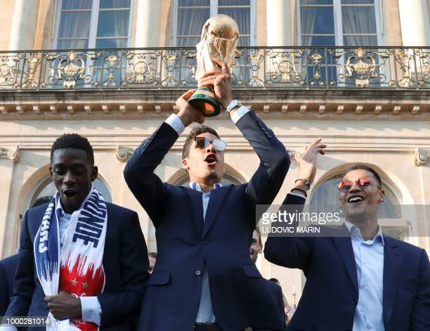 France's goalkeeper Alphonse Areola holds up the winner's trophy in the grounds of the Elysee Presidential Palace during an official reception on...