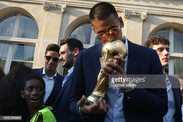 France's goalkeeper Alphonse Areola kisses the winner's trophy in the grounds of the Elysee Presidential Palace during an official reception on July...