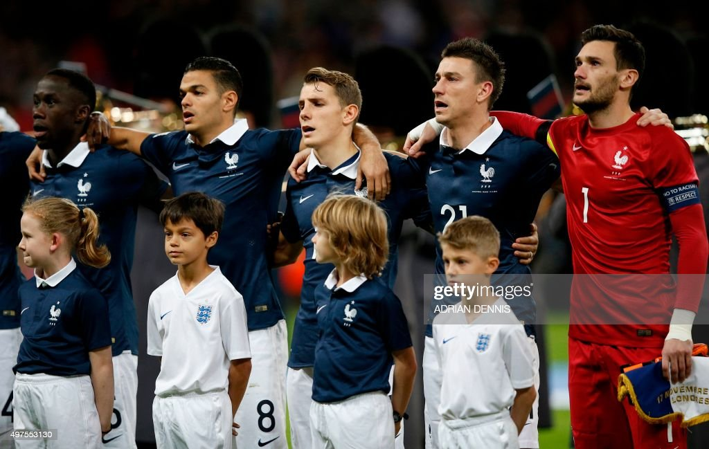 France's goalkeeper and captain Hugo Lloris, France's defender Laurent Koscielny, France's defender Lucas Digne, France's forward Hatem Ben Arfa sing their country's national anthem before the start of the friendly football match between England and France at Wembley Stadium in west London on November 17, 2015.