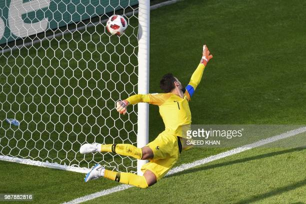France's goalkeeper Hugo Lloris dives and takes Argentina's first goal during the Russia 2018 World Cup round of 16 football match between France and...