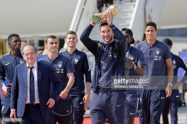 France's goalkeeper Hugo Lloris flanked by French Football Federation president Noel Le Graet and France's forward Antoine Griezmann holds the trophy...