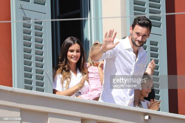 France's goalkeeper Hugo Lloris flanked by his wife Marine and his daughter AnnaRose waves to the crowd from the balcony of the townhall in his home...