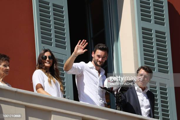 France's goalkeeper Hugo Lloris flanked by his wife Marine and Nice's mayor Christian Estrosi waves to the crowd from the balcony of the townhall in...