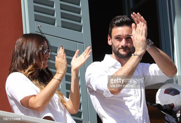 France's goalkeeper Hugo Lloris flanked by his wife Marine applauds on the balcony of the townhall in his home town of Nice southeastern France on...