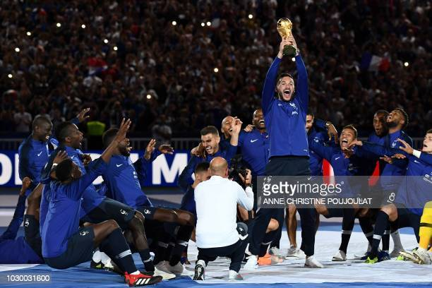 TOPSHOT France's goalkeeper Hugo Lloris holds the 2018 World Cup trophy as he celebrates with teammates during a ceremony to celebrate the victory of...