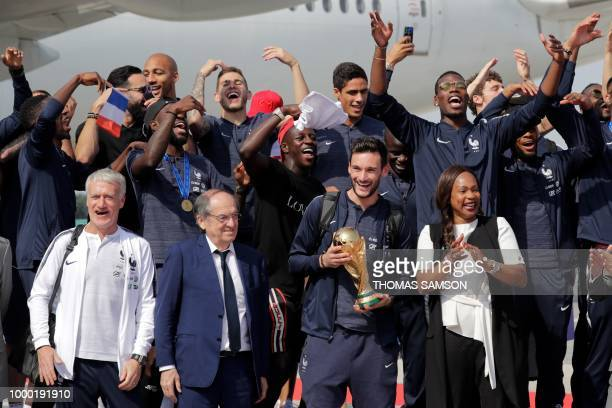 TOPSHOT France's goalkeeper Hugo Lloris holds the trophy as he celebrates with teammates and French Football Federation president Noel Le Graet...