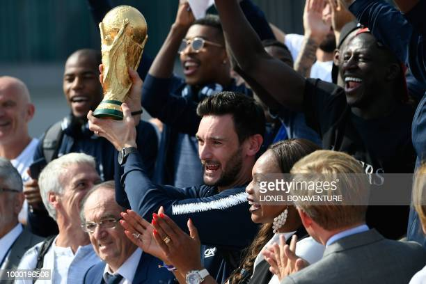 France's goalkeeper Hugo Lloris holds the trophy as he celebrates with France's coach Didier Deschamps French Football Federation president Noel Le...