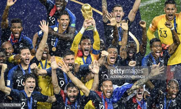 TOPSHOT France's goalkeeper Hugo Lloris holds the trophy as he celebrates with teammates during the trophy ceremony at the end of the Russia 2018...