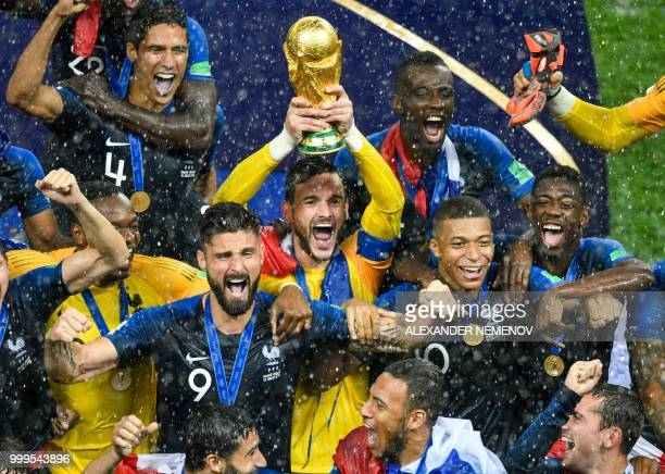 France's goalkeeper Hugo Lloris holds the trophy as he celebrates with teammates during the trophy ceremony at the end of the Russia 2018 World Cup...