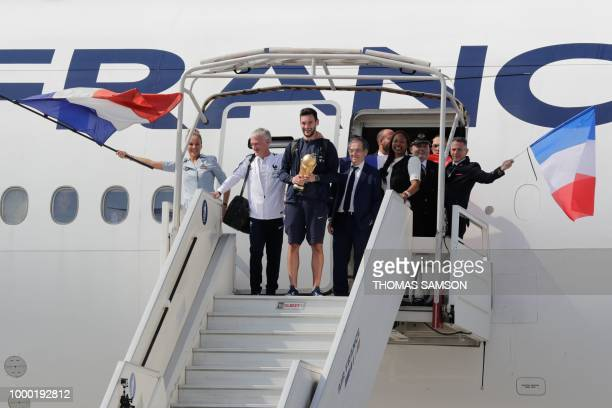 TOPSHOT France's goalkeeper Hugo Lloris holds the trophy as he disembarks from the plane next to France's coach Didier Deschamps French Football...