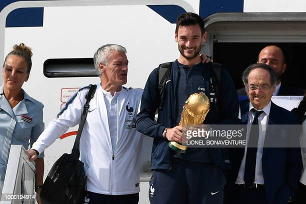 France's goalkeeper Hugo Lloris holds the trophy as he disembarks from the plane next to France's coach Didier Deschamps and French Football...
