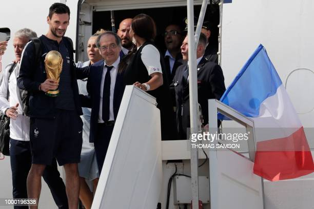 France's goalkeeper Hugo Lloris holds the trophy as he disembarks from the plane next to French Football Federation president Noel Le Graet upon...