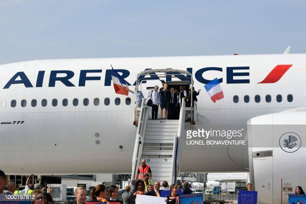 France's goalkeeper Hugo Lloris holds the trophy as he disembarks from the plane next to France's coach Didier Deschamps French Football Federation...
