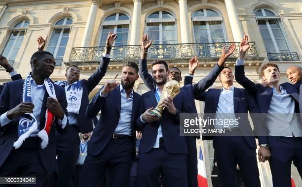 TOPSHOT France's goalkeeper Hugo Lloris holds the trophy next to France's forward Ousmane Dembele France's defender Presnel Kimpembe France's forward...