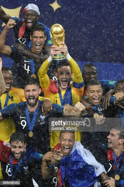 France's goalkeeper Hugo Lloris holds the trophy next to France's forward Olivier Giroud and France's forward Kylian Mbappe as they celebrate with...