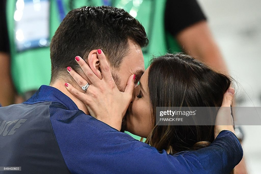 France's goalkeeper Hugo Lloris kisses his wife Marine Lloris as they celebrate the team's 2-0 win over Germany in the Euro 2016 semi-final football match between Germany and France at the Stade Velodrome in Marseille on July 7, 2016. France will face Portugal in the Euro 2016 finals on July 10, 2016 / AFP / FRANCK