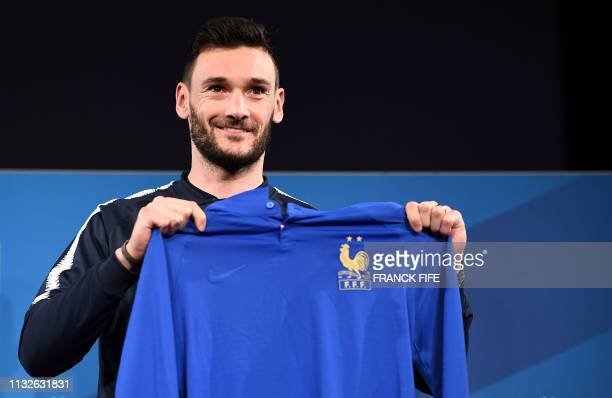 France's goalkeeper Hugo Lloris presents the jersey of the French national team celebrating the 100th anniversary of the French federation before a...