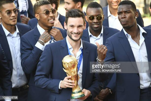 France's goalkeeper Hugo Lloris smiles and holds the trophy next to France's midfielder Paul Pogba as they arrive for a reception at the Elysee...