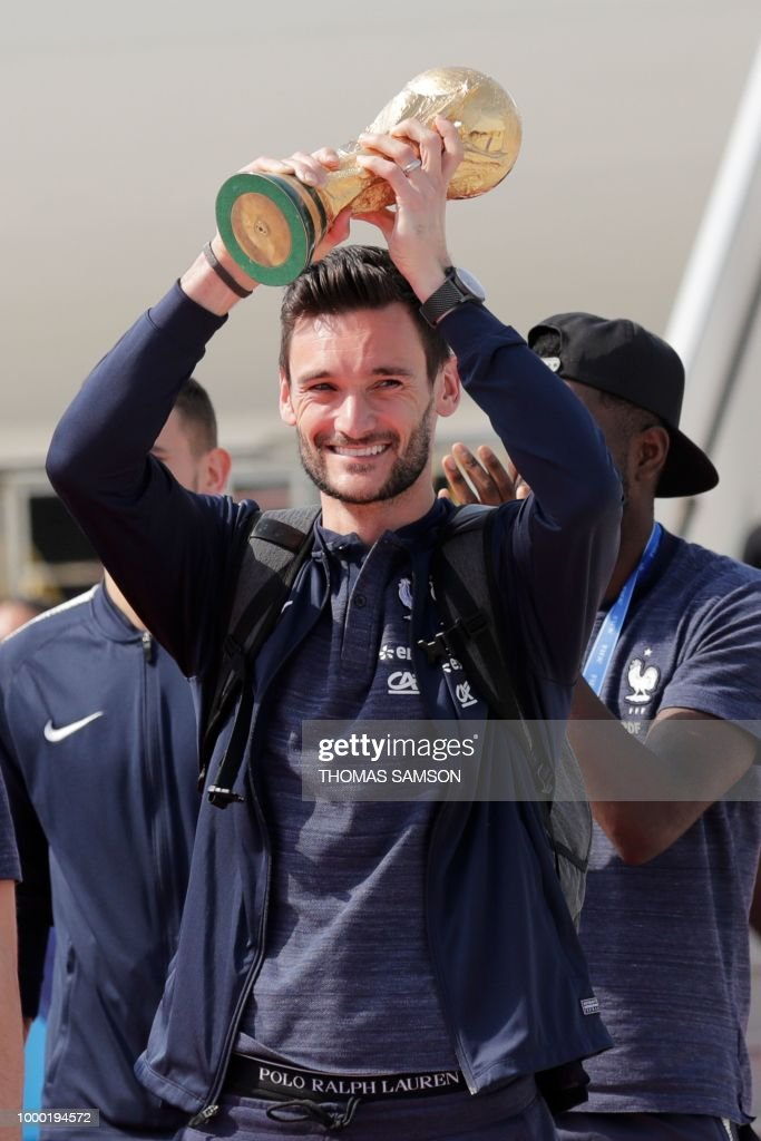 France's goalkeeper Hugo Lloris smiles as he holds the trophy as he celebrates with teammates upon their arrival at the Roissy-Charles de Gaulle airport on the outskirts of Paris, on July 16, 2018 after winning the Russia 2018 World Cup final football match.