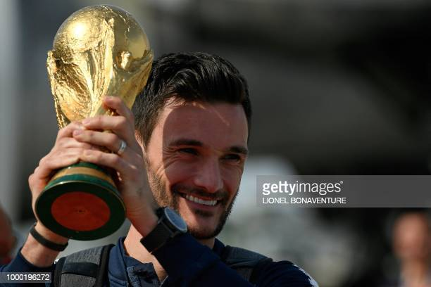 France's goalkeeper Hugo Lloris smiles as he holds the trophy as he celebrates with teammates upon their arrival at the RoissyCharles de Gaulle...