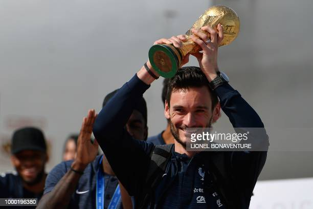 TOPSHOT France's goalkeeper Hugo Lloris smiles as he holds the trophy as he celebrates with teammates upon their arrival at the RoissyCharles de...