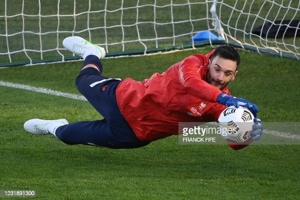 France's goalkeeper Hugo Lloris stops a ball during a training session in Clairefontaine-en-Yvelines, near Paris on March 23, 2021 on the eve of the...