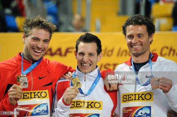 France's gold medal winner Renaud Lavillenie poses on the podium with Germany's silver medallist Bjorn Otto and bronze winner Brad Walker of the US...