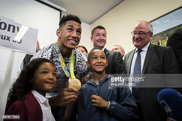 France's gold medalist in boxing at the 2016 Rio Olympics Tony Yoka poses with supporters at city hall of his hometown ChantelouplesVignes on August...