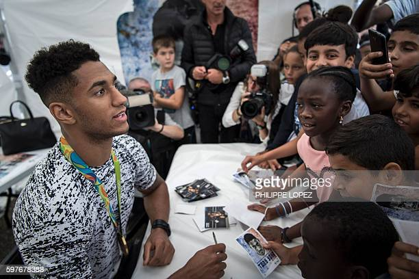 France's gold medalist in boxing at the 2016 Rio Olympics Tony Yoka signs autographs and displays his medal to supporters at city hall of his...