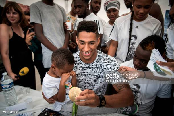 France's gold medalist in boxing at the 2016 Rio Olympics Tony Yoka displays his medal to supporters at city hall of his hometown ChantelouplesVignes...
