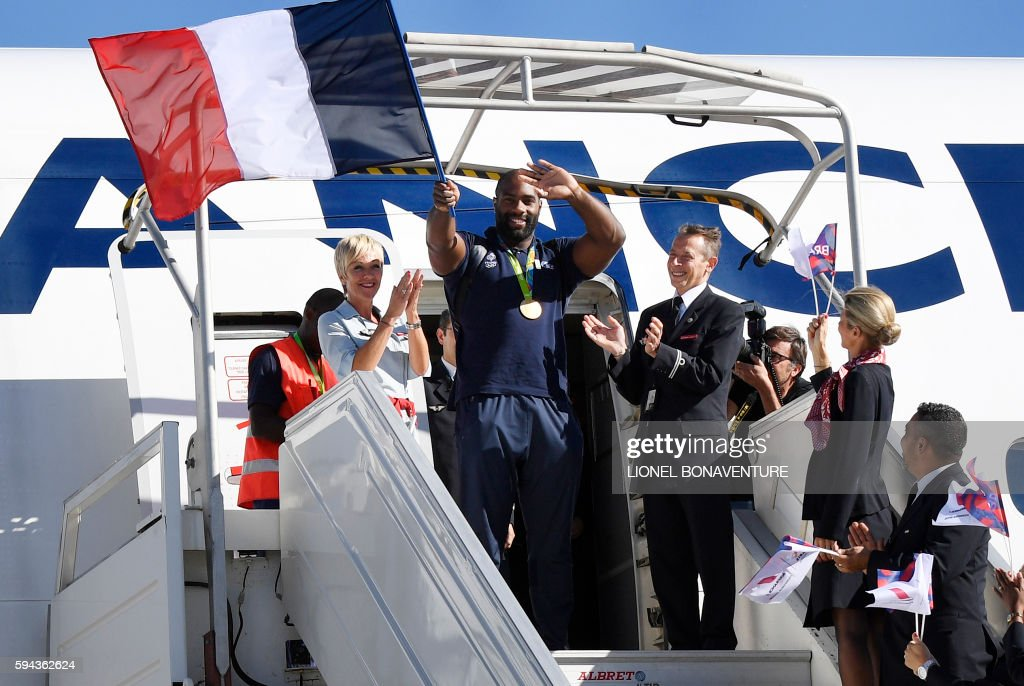 TOPSHOT - France's gold medalist judoka Teddy Riner (C) waves a French flag as he steps off the plane on the Roissy-Charles-De-Gaulle airport's tarmac near Paris on August 23, 2016 as the France's olympic returns to France after the 2016 Rio olympic games. The French Olympic team comes back to France with a total of 42 medals, a post world war II record after Beijing's 41 podiums. In the detail, French athletes won 10 gold, 18 silver, and 14 bronze medals. / AFP / Lionel BONAVENTURE / ALTERNATIVE