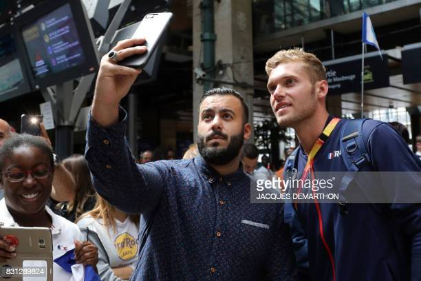 TOPSHOT France's gold medallist and decathlon athlete Kevin Mayer takes a selfie with a fan as he arrives at the Gare du Nord in Paris on August 14...