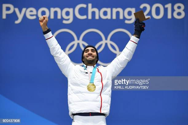 France's gold medallist Martin Fourcade celebrates on the podium during the medal ceremony for the biathlon men's 15km Mass Start at the Pyeongchang...