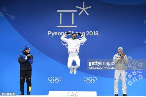 TOPSHOT France's gold medallist Martin Fourcade jumps on the podium between Sweden's silver medallist Sebastian Samuelsson and Germany's bronze...