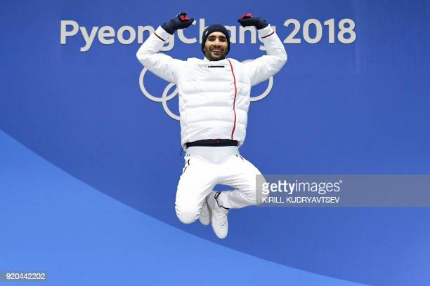TOPSHOT France's gold medallist Martin Fourcade jumps on the podium during the medal ceremony for the biathlon men's 15km Mass Start at the...