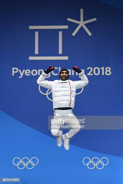 France's gold medallist Martin Fourcade jumps on the podium during the medal ceremony for the biathlon men's 15km Mass Start at the Pyeongchang...
