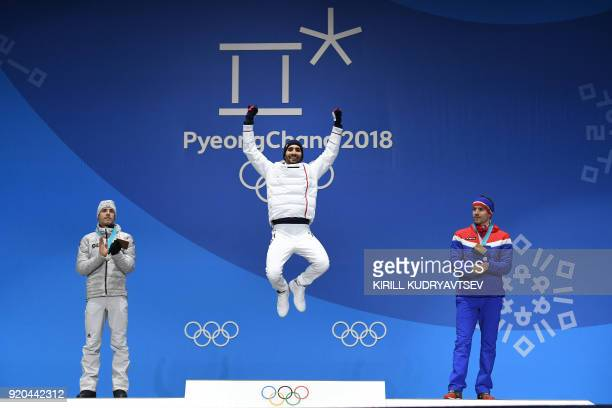 France's gold medallist Martin Fourcade jumps on the podium next to Germany's silver medallist Simon Schempp and Norway's bronze medallist Emil Hegle...