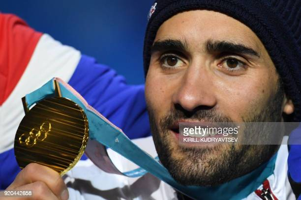 France's gold medallist Martin Fourcade poses on the podium during the medal ceremony for the biathlon men's 15km Mass Start at the Pyeongchang...