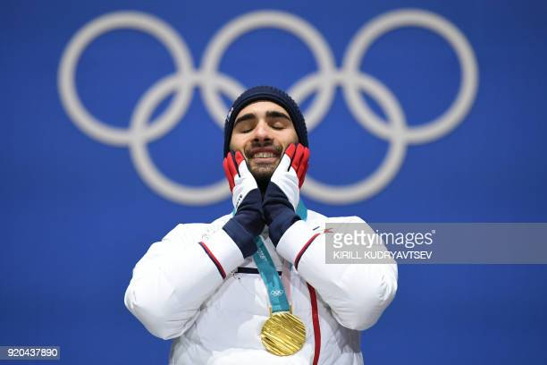 TOPSHOT France's gold medallist Martin Fourcade reacts on the podium during the medal ceremony for the biathlon men's 15km Mass Start at the...