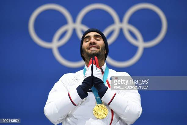France's gold medallist Martin Fourcade reacts on the podium during the medal ceremony for the biathlon men's 15km Mass Start at the Pyeongchang...
