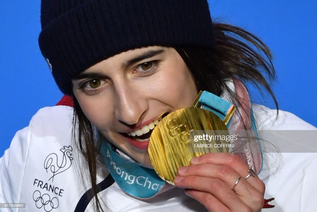 TOPSHOT - France's gold medallist Perrine Laffont bites her medal on the podium during the medal ceremony for the women's freestyle skiing moguls at the Pyeongchang Medals Plaza during the Pyeongchang 2018 Winter Olympic Games in Pyeongchang on February 12, 2018. / AFP PHOTO / Fabrice COFFRINI