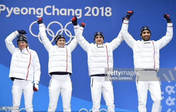 France's gold medallists Marie Dorin Habert, Anais Bescond, Simon Desthieux and Martin Fourcade pose on the podium during the medal ceremony for the...