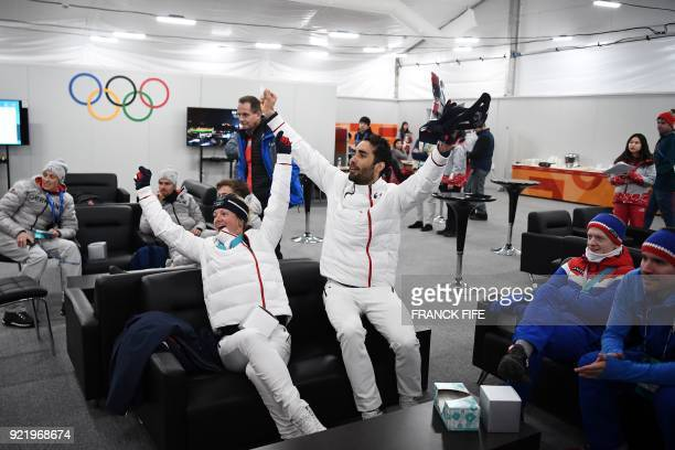 France's gold medallists Marie Dorin Habert and Martin Fourcade react while watching a live broadcast of the French team winning third place in the...