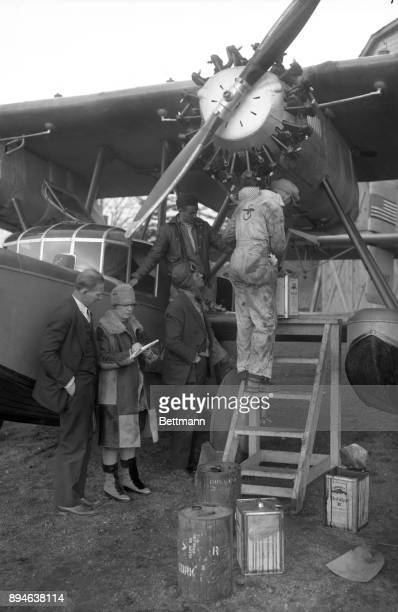 Frances Grayson and Brice Goldsborough reading weather report as Lt Oskar Ondal watches mechanics get the plane ready for dropoff at Roosevelt Field