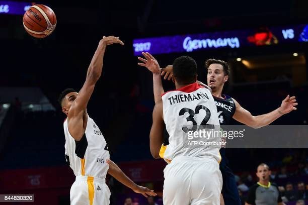 France's guard Thomas Heurtel vies with Germany's guard Dennis Schroder and Johannes Thiemann during the FIBA Eurobasket 2017 men's round 16...