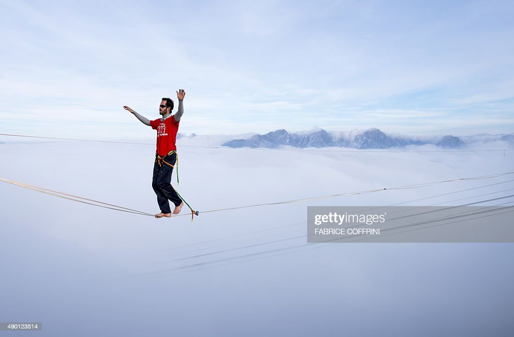 France's Guillaume Rolland walks on the line during the Highline Extreme event in Moleson peak, western Switzerland on September 26, 2015. Fifty of the European best slackliners compete until September 27, 2015 on six different lines ranging from 45 metres to 495 metres.